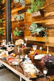 An Eclectic Cheese And Prosciutto Station With Assorted Fruit Displayed Against A Wall Of Wild Succulents