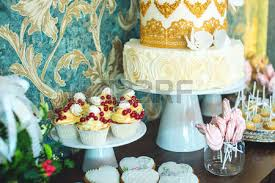 Luxury wedding candy bar with a beautiful white cake decorated with gold ornaments The concept