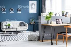 dunkel blau wohnzimmer interieur mit drei uhren einfache poster helles sofa und homeofficeecke mit laptop auf haarnadel schreibtisch stockfoto und