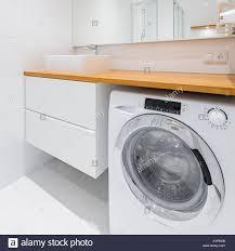 weißes badezimmer mit holz arbeitsplatte waschbecken