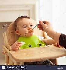 Baby Boy In High Chair Being Spoon-fed, Wearing Plastic Bib ... Baby Our Midcentury Modern Micuna Ovo City High Chair Cute Baby Child Eats Healthy Food Portrait Of Happy Kid Boy The Essential Kit For Weaning Parents Tidy Tot Bibado Bib Review Is It The Best Led Long Sleeve Amazoncom Sunshinetimes Feeding And Tray Saucer Girl Wearing Sitting In Highchair Toddler Anti Dirty Mat African Descent Eating Apple Stock Wearing Blue Jumpsuit White Bib Sitting In