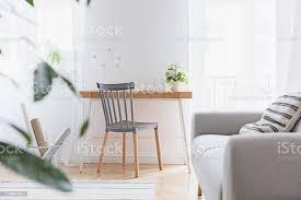 modernes skandinavisches wohnzimmer mit designmöbeln grauem sofa pflanzen bambusbuchständer und holztisch braunes holzparkett schöne wohnung