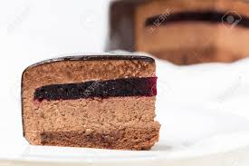 Slice of chocolate mousse cake with currant jelly and mirror glaze Stock