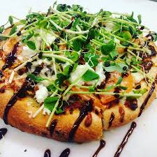 boreal cuisine boreal veggie pizza topped with local sunflower and pea shoots