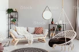 hängesessel in der nähe grauen holzsofa ethno wohnzimmer interieur mit runder spiegel echtes foto stockfoto und mehr bilder boho stil