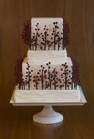 A Square White Wedding Cake With Rustic Branches