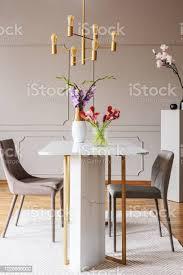 blumen am tisch in grau esszimmer interieur mit gold le und stühlen auf teppich echtes foto stockfoto und mehr bilder blume