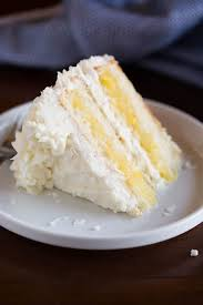 A slice of Coconut Cake with pineapple filling laying on a white plate