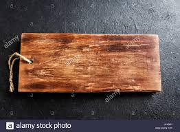 Rustic Wooden Cutting Board On Black Stone Background Close Up