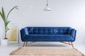 blaues sofa und wicker teppich in weißes einfaches wohnzimmer