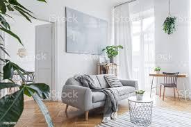 stilvolles skandinavisches wohnzimmer mit designmöbeln pflanzen bambusbüchertisch und holztisch braunes holzparkett abstrakte malerei an der weißen