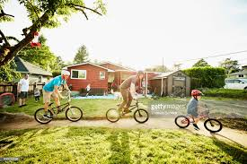 Family And Friends Riding Bikes Playing In Backyard On Summer Evening Stock Photo