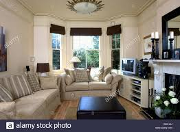 Beige Sofas In Cream Living Room With Black Blinds On Bay Window And Television Shelf Unit Beside Fireplace