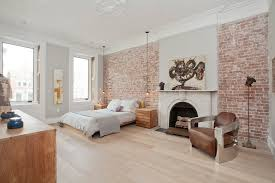 Cozy Bedroom Design Ideas With Exposed Brick Wall And Art Above Arched Fireplace Metal Armchair Platform Bed Ceiling Medallion Crown