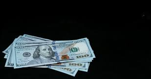 Hundred Dollar Bills Falling Fast A Black Wooden Table Stock