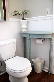 A Small End Table Placed Above Toilet Paper Roll Is Cool Bathroom Storage Hack
