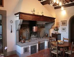 An Italian Country Kitchen With The Open Fireplace