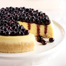 Platter with vanilla mascarpone blueberry cheesecake with a slice taken out of it