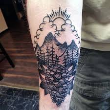 Guy With Forearm Black Ink Tattoo Pine Cone And Sun Behind Mountains