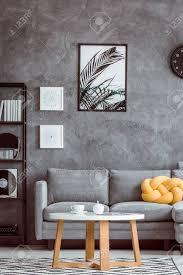 malerei blättern auf dunkler wand über grauem sofa mit gelbem kissen im einfachen wohnzimmer