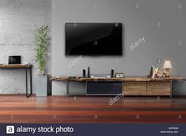 led tv auf graue wandfarbe mit holztisch und plant in pot