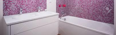 modernes badezimmer mit weißen möbeln und rosa fliesen