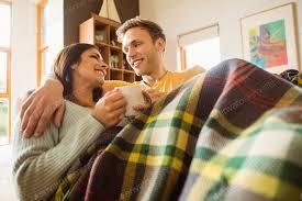 junges paar kuscheln auf der unter decke zu hause im wohnzimmer foto wavebreakmedia auf envato elements
