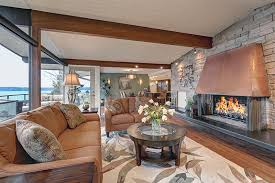 Rustic Waterfront Living Room With Large Copper Fireplace Rock Accent Wall And Wood Beams