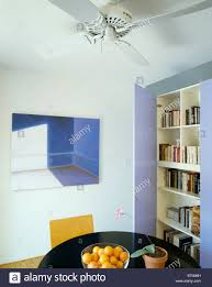 Large Picture On Wall Of Modern Dining Room With Electric Ceiling Fan Above Table And Fitted Bookshelves Mauve Doors