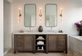 brown wooden vanity with frame and sleek wall lights