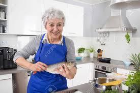 femmes plus cuisine une femme plus âgée aux cheveux gris dans la cuisine préparer le