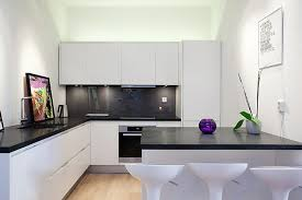 Ultra Modern Kitchen Design With Luxurious Black Countertop And White Cabinets A Counter Island Barstools Unfinished Wood Floors Good Inspirations Light