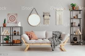 makramee spiegel und ethnografik auf beige wand im stilvollen wohnzimmer interieur mit möbel aus metall und bequeme und gemusterten kissen und