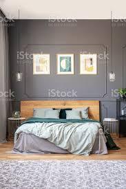 poster auf graue wand mit formteil über hölzerne bett im modernen schlafzimmer inneren echtes foto stockfoto und mehr bilder bett