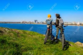 Happy Young Female Friends Riding Bicycles On The Seaside Road Women Enjoying Bikes