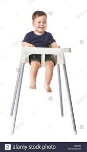 Cute Baby Boy Sitting In High Chair Against White Background ...
