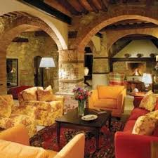 Tuscan Living Room With Archway Brick Pilars And Patterned Rug Colorful Seating Floor Lamp
