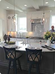 the gray island with the white cabinets and the light fixture