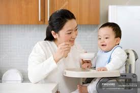 Chinese Woman Feeding Baby Son In High Chair In Kitchen ... Young Woman Leaning On High Chair By Table With Glass Of Baby Shopping Cart Cover 2in1 Large Beautiful Woman Sitting On A High Chair In The Studio Fashion How To Plan Wonder Themed 1st Birthday Party First Elegant Young Against Red Stock Photo Artzzz Fenteer Nursing Cushion Women Kids Carthigh Business Sitting Edit Now Over Shoulder View Of Otographing Baby Daughter Stock Photo Metalliform 2104 Polyprop Classroom 121