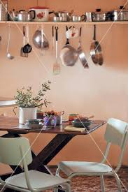 Pots Pans And Kitchen Utensils On Wall Mounted Shelf Above Dining Table In