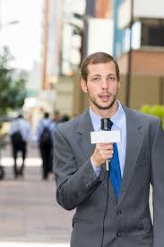 Attractive Professional Male News Reporter Wearing Grey Suit Holding Microphone Talking To Camera From Urban