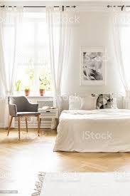 graue sessel am fenster mit vorhängen in weiße schlafzimmer innenraum mit plakat über dem bett echtes foto stockfoto und mehr bilder bett
