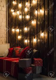holz zimmer im rustikalen haus mit holzwand und designer glühbirnen dekoriert platz für sitz rote graue kissen