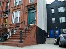 historic bed stuy brownstone has wall painted black by neighbor