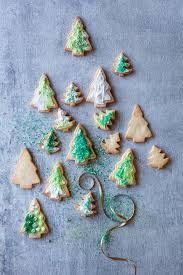 Christmas Tree Cookies Decorated With Green Edible Glitter And Festive Sprinkles By Nadine Greeff For Stocksy