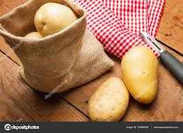 Potatoes In A Burlap Bag And Potatoe Peeler Stock Photo