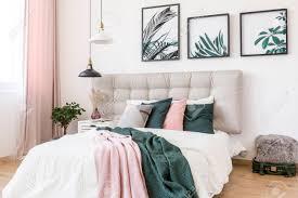 schwarzweiss le über bett mit rosa und grüner decke gegen eine wand mit galerie blattplakaten im hoch entwickelten schlafzimmerinnenraum