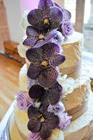 Purple Orchids And Roses Adorn This Roughly Textured Wedding Cake Coated With White Chocolate Ganache