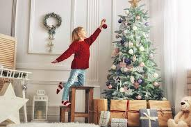 Young Girl Putting Ornament On Tall Christmas Tree
