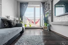 licht wohnzimmer in grau und weiß mit sofa großer fernseher und balkon